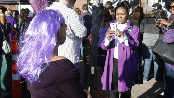 A Prince fan, right, shoots a photo of another fan with purple hair as fans gather outside Xcel Arena on Thursday, Oct. 13, 2016, in St. Paul before a concert honoring the musician who died in April of accidental overdose.