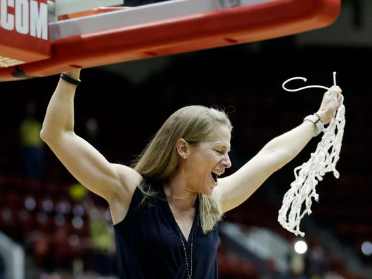 Michigan's Kim Barnes Arico cuts the net after the WNIT championship game against Georgia Tech at Calihan Hall.
