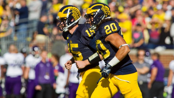 Michigan quarterback Jake Rudock (15) and running back Drake Johnson run off the field together after scoring a touchdown against Northwestern in Ann Arbor on Saturday, Oct. 10, 2015.