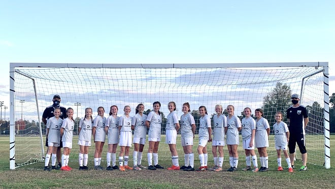 """The CFC 08 Hendersonville team recently wrapped up an undefeated season. Pictured from left to right are Head coach Adam Payne, Maleia Eldreth, Olivia Austin, Virginia Oakman, Macy Rogers, Reagan """" Lefty"""" Simons, Sawyer Manuel, Ava Payne, Ella Pavao, Ella """" KJ"""" Collier, Sarah Love, Reese Smith, Reagan Adams, Caroline Coggins, Adrianna Denny, Leah Williams, Jena Denny and Assistant Coach Bryan Adams. Not Pictured: Anarose Kozlowski."""