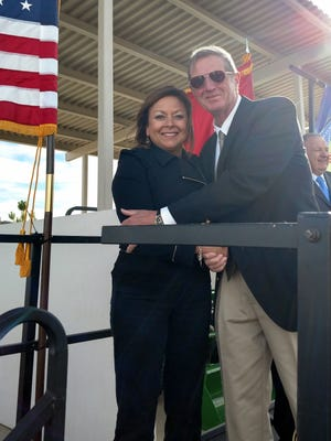 Lincoln County Commissioner Tom Stewart and retired military, gives Gov. Susana Martinez a warm hug in the chilly wind blowing at the officials opening of the veterans cemetery at Fort Stanton.
