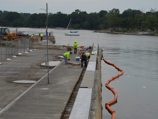 Construction workers rebuild the seawall at Hudson