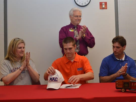 Pineville High School's Christian Adams (center) signed with Macalester College in Minnesota in February 2014. With him are mom Kathy Melancon (left), dad Jeff Adams (right) and Pineville High School principal Karl Carpenter (back).