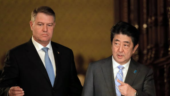 Japanese Prime Minister Shinzo Abe, right, walks with