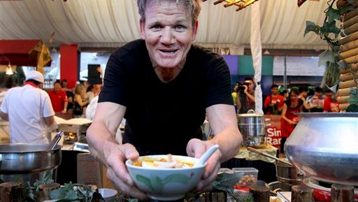 """In this file photo, celebrity Michelin-starred chef Gordon Ramsay serves up a bowl of """"Laksa"""" a local noodle dish which he prepared at the famous tourist food center, Newton Circus Hawker Center, in Singapore. Ramsay is facing a kitchen nightmare after a British judge on Tuesday  ruled him personally liable for rent on a London gastropub."""