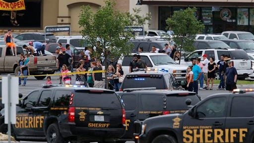 "People at the Central Texas MarketPlace watch a crime scene near the parking lot of a Twin Peaks restaurant Sunday, May 17, 2015, in Waco, Texas. Waco Police Sgt. W. Patrick Swanton told KWTX-TV there were ""multiple victims"" after gunfire erupted between rival biker gangs at the restaurant."