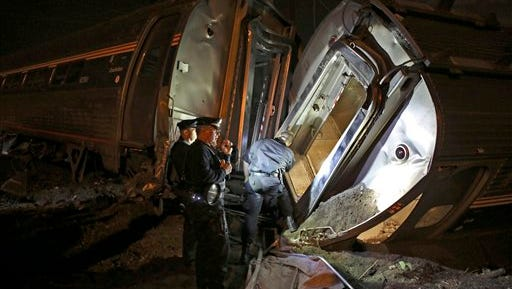 FILE - In this May 12, 2015 file photo, emergency personnel work the scene of a train wreck An Amtrak train headed to New York City derailed and crashed in Philadelphia. Amtrak says it will install video cameras inside locomotive cabs that record the actions of train engineers. The move follows a deadly derailment earlier this month in which investigators are searching for clues to the train engineer's actions just before the crash. (AP Photo/Joseph Kaczmarek, File)