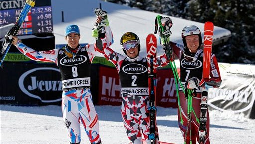 First place finisher Austria's Marcel Hirscher, center, celebrates while posing for photos with second place finisher France's Victor Muffat-Jeandet, left, and third place finisher Norway's Henrik Kristoffersen at the men's World Cup giant slalom ski race Sunday, Dec. 6, 2015, in Beaver Creek, Colo. (AP Photo/Brennan Linsley)
