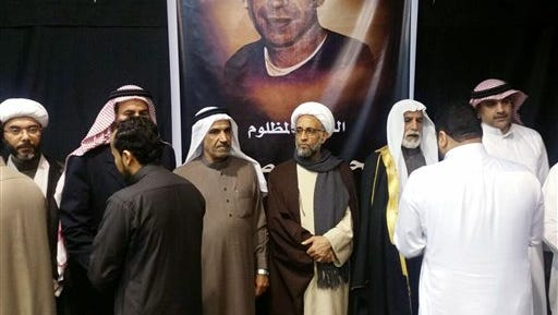 In this picture taken Tuesday, Jan. 5, 2016, by a citizen journalist, which has been verified and is consistent with other AP reporting, Sheikh Hassan al-Saffar, a top Shiite cleric from Qatif, center, stands with family members of Shiite Sheikh Nimr al-Nimr and other Shiite notables, as they receive condolences on the second day of mourning for him at a mosque in the village of al-Awamiya, eastern Saudi Arabia. Al-Nimr was an outspoken critic of Saudi Arabia's Sunni monarchy but denied ever calling for violence. His execution on Saturday has sparked outrage among Shiites across the region. The poster behind the men shows Mohammed Ali Abdulkarim Suwaymil a young Saudi Shiite who was executed at the same time as al-Nimr. (verified UGC via AP)