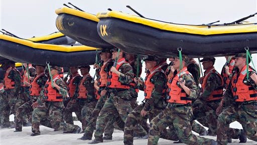 In this May 14, 2009 file photo, Navy SEAL trainees carry inflatable boats at the Naval Amphibious Base Coronado in Coronado, Calif. Navy SEAL teams don't have enough combat rifles to go around even as these secretive, highly trained forces are relied on more than ever to hunt down members of the Islamic State group and other terrorists, according to SEALs who have confided in Rep. Duncan Hunter, R-Calif.