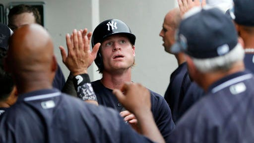 New York Yankees' Ben Gamel is congratulated in the dugout after scoring on a Minnesota Twins' Ervin Santana balk in the fifth inning a spring training baseball game, Sunday, March 20, 2016, in Fort Myers, Fla.