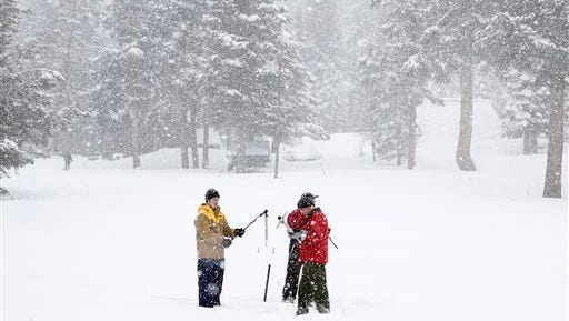 Officials measure the snowpack near Echo Summit in February.