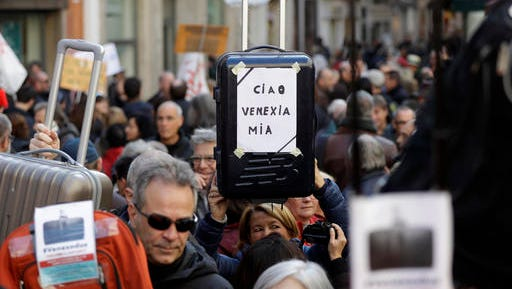 Demonstrators holding suitcases protest against the increasing number of tourists in Venice, Italy, Saturday, Nov.12. 2016. For decades, the number of Venetians have dwindled steadily and numerous factors are blamed _ high prices driven by a boom in tourism and the logistics of supplying a carless city and erosion by lapping waters among them. The banner reads 'Goodbye my Venice""