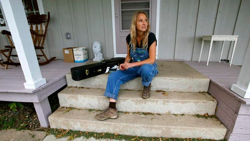 """In this Oct. 3, 2016 photo, singer Lissie Maurus sits on her front porch at her Iowa farm. Maurus moved to Iowa from southern California after losing her record deal. She released an album """"My Wild West,""""this year has and a strong following in the UK, Norway and in her native Midwest."""