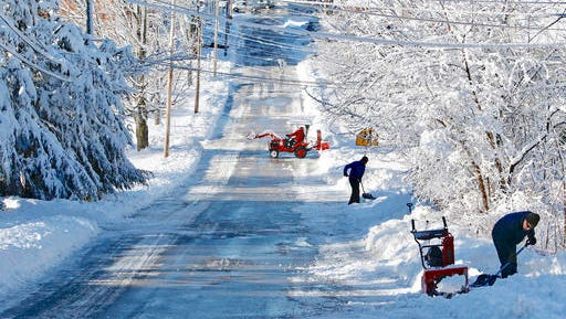 Residents along Paul Street clear snow from their driveways in South Berwick, Maine, Friday, Dec. 30, 2016, after 5-6 inches of wet, heavy snow fell overnight. The most powerful nor'easter in nearly two years brought heavy snow, powerful winds and even thunder and lightning to northern New England, leaving tens of thousands of people in the dark Friday and burying some towns under 2 feet of snow.