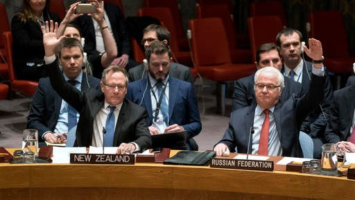 New Zealand's U.N. Ambassador Gerard van Bohemen, left, and Russia's ambassador to the U.N., Vitaly Churkin, raise their hands as they join other members of the Security Council at the United Nations headquarters on Saturday, Dec. 31, 2016, voting to pass a resolution supporting efforts by Russia and Turkey to end violence in Syria and jumpstart peace negotiations.