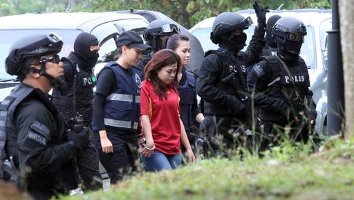 Indonesian suspect Siti Aisyah, center, in the ongoing assassination investigation, is escorted by police officers as she arrives at Sepang court in Sepang, Malaysia on Wednesday, March 1, 2017. Under the protection of special forces carrying machine guns, two women accused of smearing VX nerve agent on Kim Jong Nam, the estranged half brother of North Korea's leader, arrived in court Wednesday to face murder charges.