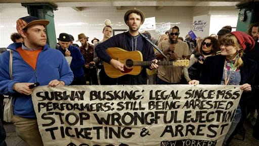 Andrew Kalleen joins other performers during a protest in the Metropolitan Avenue Subway station Tuesday in New York. Kalleen, 30, was performing Friday at the G-train stop in Brooklyn's hipster Williamsburg neighborhood when an officer told him he must leave the station because he needs a permit to play there. The New York Police Department says it's looking into the arrest.