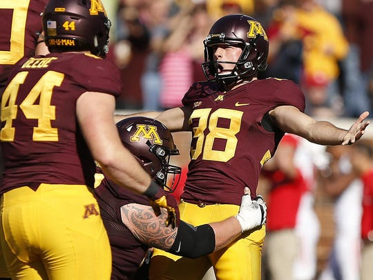 Minnesota kicker Emmitt Carpenter stretches out his arms in celebration after kicking a game-winning field goal.