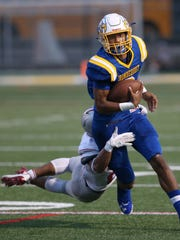 Irondequoit quarterback Freddy June Jr. is tackled from behind by Canandaigua's AJ Clifford as he scrambles downfield for yardage.