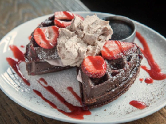 The dark chocolate waffle at Saint Anejo with a strawberry crema drizzle, topped with sweet cinnamon whipped cream
