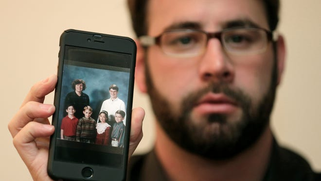 Jamey Anderson holds a photo on his phone of himself, bottom left, at the Word of Faith Christian School with classmates, from left, Liam, Risa Burgeson Pires, and Christopher Davies, and teachers Lisa Brown, top left, and Marty Roper, top right, during an interview in Charlotte, N.C., Monday, Dec. 11, 2017. Throughout his adolescence, Anderson says he was singled out as a rebel and suffered some of the most brutal treatment in the church. Among his transgressions: making a funny face at a classmate.