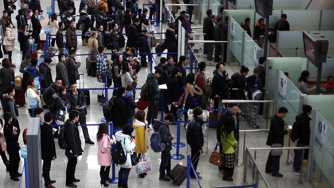 In this Jan. 20, 2012, file photo, passengers queue up for a security check at Pudong International Airport in Shanghai.