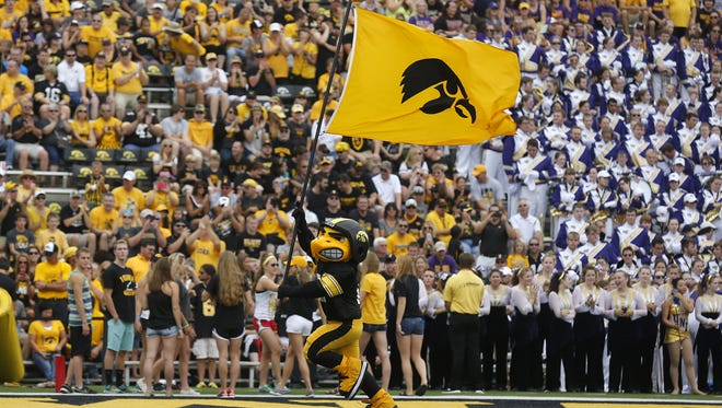 Herky runs with the Hawkeye flag against Northern Iowa on Saturday, Aug. 30, 2014, at Kinnick Stadium in Iowa City, Iowa.