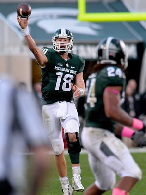 MSU quarterback Connor Cook hits running back Gerald Holmes for a first down after a scramble against Indiana            Saturday 10/24/2015.