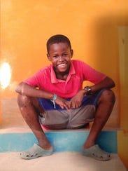 Rivaldo Hill is shown as a boy in Haiti. He was taken