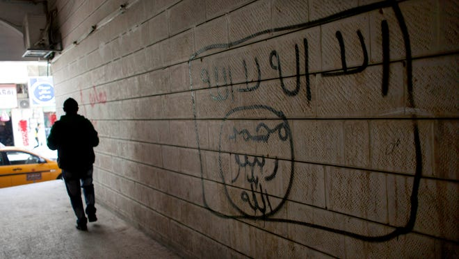 "A man walks past a graffiti depicting the flag of the Islamic State group with Arabic words that reads, ""Their is only one God and Muhammad is his prophet,"" in Ma'an, Jordan, on Dec. 12, 2014."