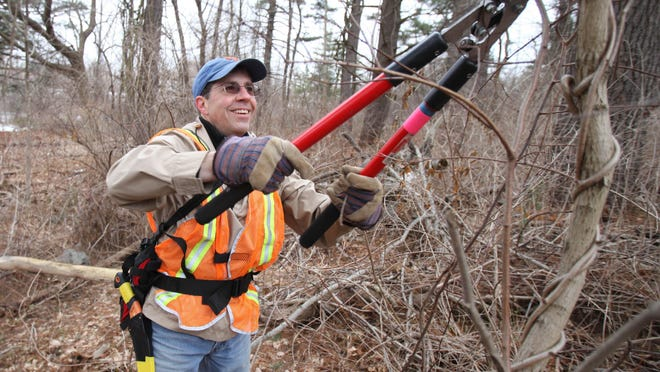 Rick Zottola of the Bronx River Parkway Reservation Conservancy cuts vines on March 28 near the North White Plains Metro-North parking lot. One driver on the nearby Bronx River Parkway says overgrowth makes the roadway dangerous.