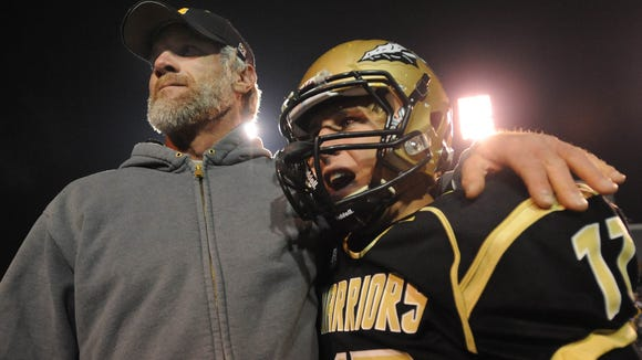 Oak Grove quarterback Kirk McCarty (17) celebrates with assistant coach Brett Favre after defeating Tupelo 14-7 for the 6A State Championship title.