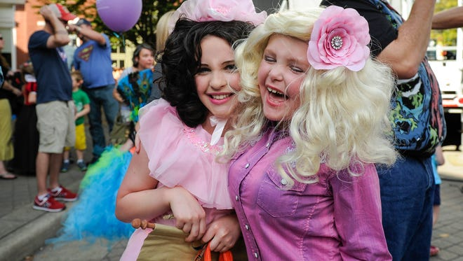 """London Dendy, left, dressed as a """"Munchkin"""" and friend London Bradley, dressed as """"Dolly Parton"""" laugh after winning first and second place in a costume contest during the 2016 Pumpkinfest in Franklin. This year's festival will be Saturday, Oct. 28, in downtown Franklin."""