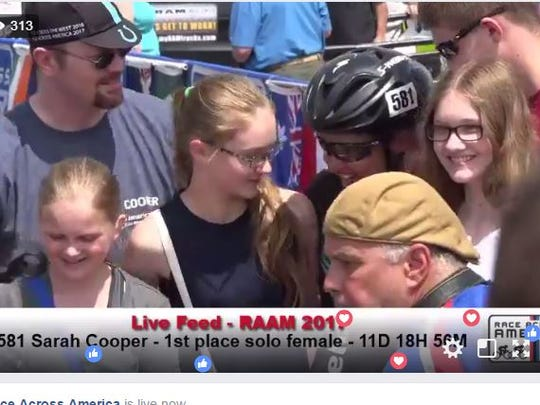 Sarah Cooper is surrounded by her husband and children at the finish line for the Race Across America on Sunday, June 25, as shown during a livestream broadcast.