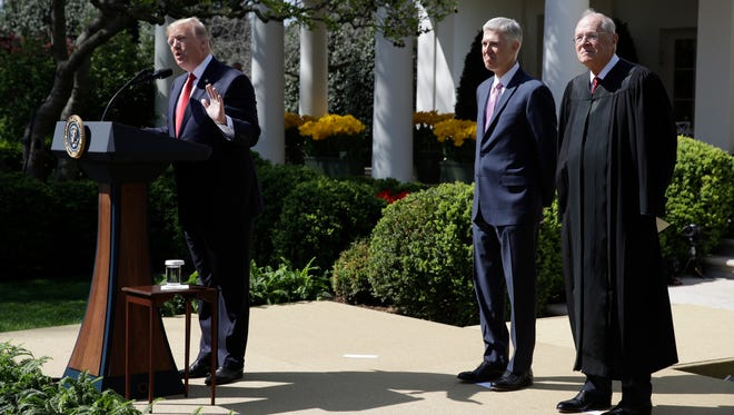 President Trump, accompanied by Justice Anthony Kennedy, right, and Justice Neil Gorsuch, speaks in the Rose Garden of the White House on April 10, 2017, before a public swearing-in ceremony for Gorsuch.