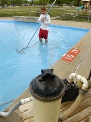 A St. Cloud Park Department employee vacuums the wading