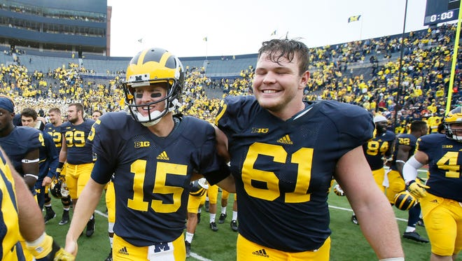 Michigan quarterback Jake Rudock and offensive lineman Graham Glasgow walk off the field after their 35-7 win over Oregon State at Michigan Stadium on Saturday, September 12, 2015, in Ann Arbor.