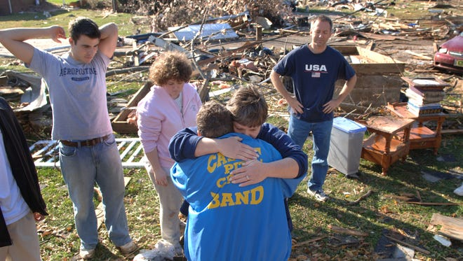 JASON CLARK / Courier & Press Archives Melinda Pipes offers a hug to Barb Bullock, bottom as friends and family members offer support and help after the Bullock family survived the early morning tornado while inside of their home on Taylor Ave., in Newburgh on Sunday.  Also pictured in the background from left are Mike Downey, Nikki Bullock and Dennis Skinner all of Newburgh.