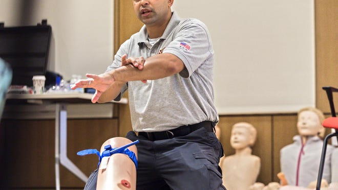Lt. Cesar Lora, firefighter/paramedic with Palm Beach Fire Rescue, demonstrates how to apply pressure to a bleeding wound during a training session for the Stop the Bleed program in 2017.