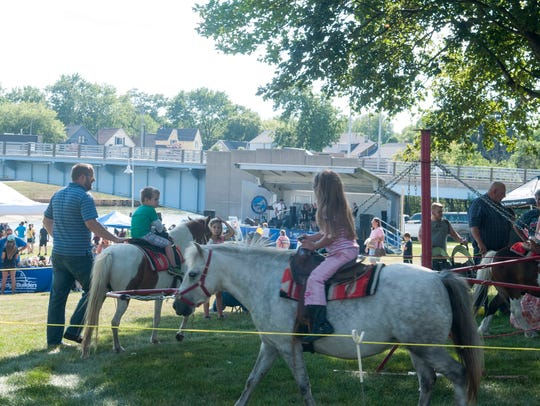 Children take pony rides as a band plays along the