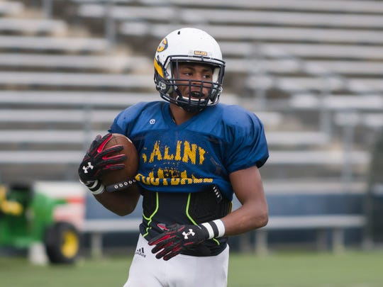 Saline defensive back MJ Griffin runs with the ball during practice.