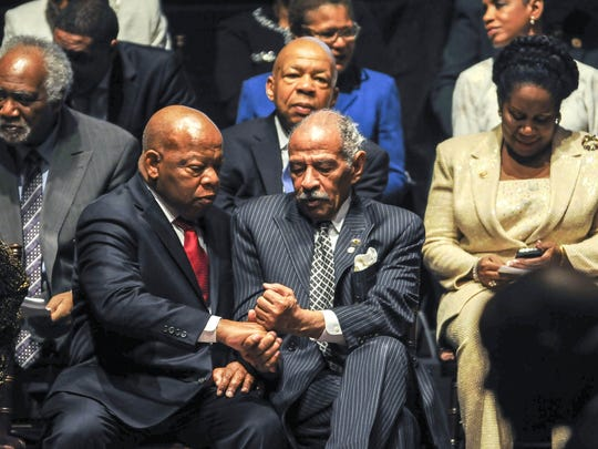 Rep. John Conyers (D-MI) gives Rep. John Lewis (D-GA) a fist bump during the Congressional Black Caucus swearing-in ceremony at the U.S. Capitol on January 6, 2015 in Washington, D.C.
