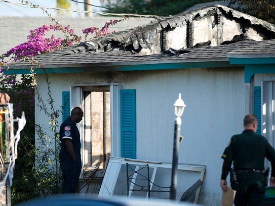 Investigators gather at a house fire on Beach Avenue