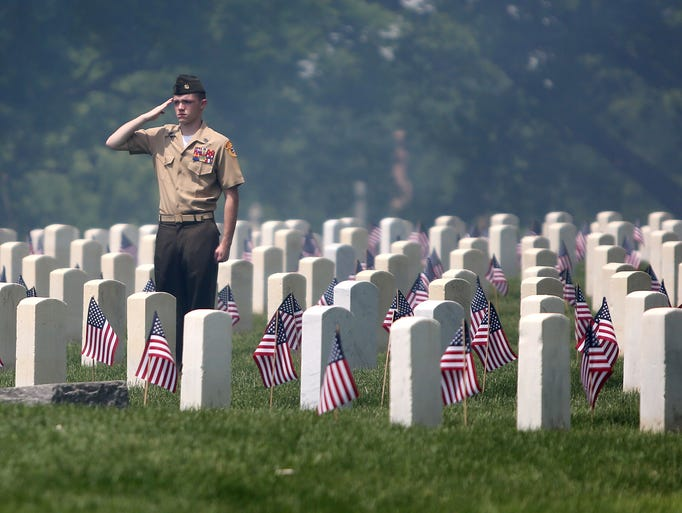 Travis Long, with the Central Indiana Young Marines Color Guard, stands and salutes as the American flag is lowered to half staff, a 21-gun salute and taps are performed, during the 146th Observance of Memorial Day at Crown Hill National Cemetery, Monday, May 26, 2014.