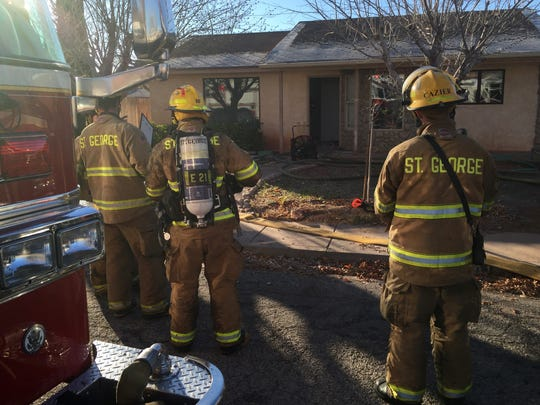 St. George Fire Department firefighters look on as a fan blows smoke out of an unoccupied home on 1400 North in St. George early Friday morning, Dec. 18, 2015.