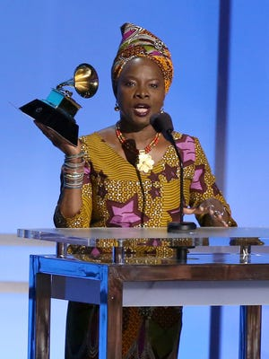 """Angelique Kidjo accepts the award for best world music album for """"Sings"""" at the 58th annual Grammy Awards on Monday in Los Angeles."""
