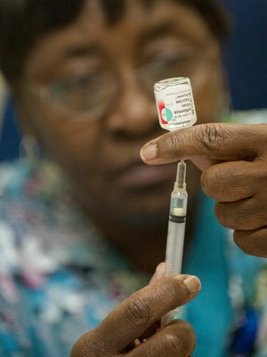 Louisville Public Health registered nurse Jean Hightower draws a dose of flu vaccine from its vial. (Crouch is in his 70's.) Oct. 09, 2013