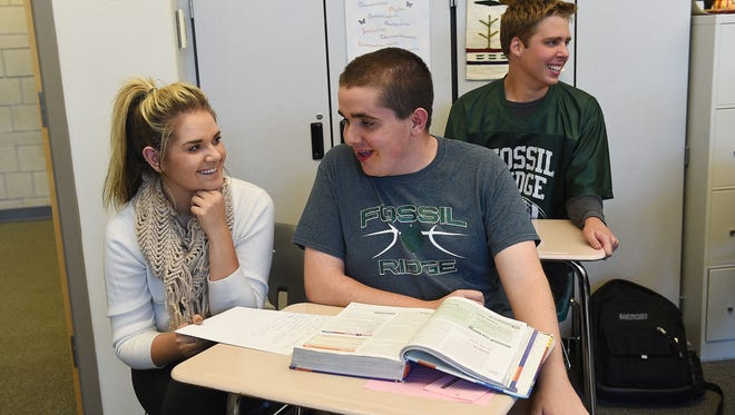 Peter Cifaloglio talks with Josie Swarbrick, paraprofessional for integrated services, in his world history class at Fossil Ridge High School on Wednesday, October 5, 2016. Swarbrick attends classes with and assists special needs students Cifaloglio and Dawson Coker, in back.
