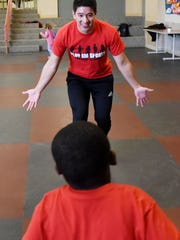 Grant Williams encourages a student to run at First Beginnings Child Development Center at First United Methodist Church. Williams works with PlayEm Sports, an organization that brings physical activity and exercise to kids at local daycare and summer programs.